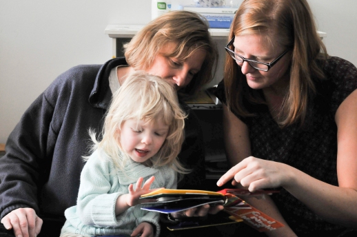 Graduate student Abigale Stangl (right), a CU-Boulder doctoral student and a volunteer at the Anchor Center for Blind Children in Denver, shows a young Anchor Center student and her mother a 3D version of Goodnight moon. (Photo by Casey A. Cass/University of Colorado)